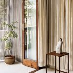 Simple And Ultramodern Space Wood Framed Glass Door With Dramatic Curtains On Either Sides Simple Modern Side Table With Metal Legs Woven Pot For Houseplant