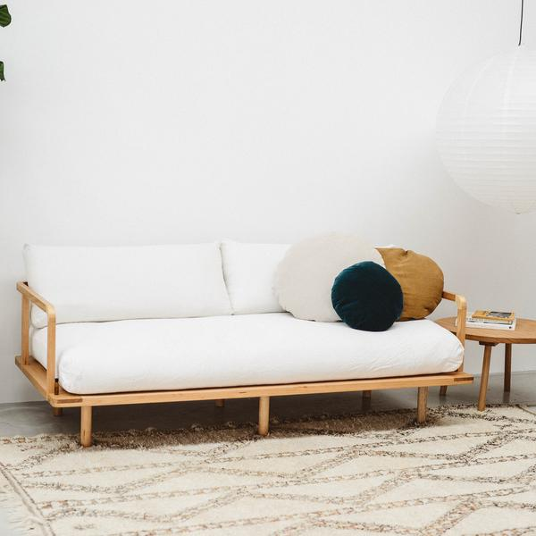 simple minimalist futon couch in white with wood frame round throws in white and deep blue fabric area rug with ethnical patterns