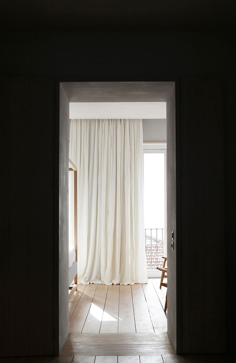 small part of bedroom with exposed curtains in white wood floors