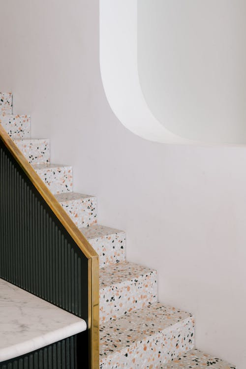 terrazzo staircase with wood handle and black railings