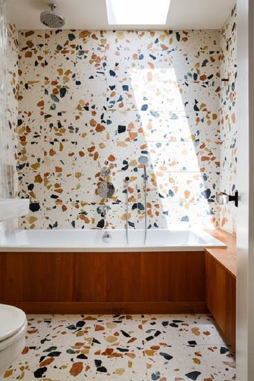 terrazzo tiles floors and walls built in bathtub with wood side panel