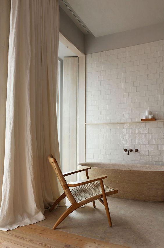 warm and relaxed feel bathroom gloss subway tile walls in white wood floors dramatic curtains in broken white simple wood chair wood like bathtub gray rug
