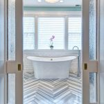Wooden Herringbone Patterned Floors White Subway Tile Walls Classic Bathtub In White Standing Shower Faucet