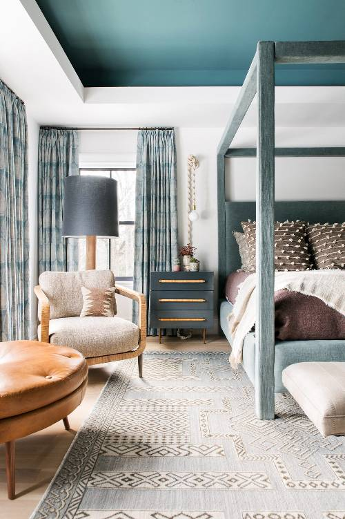 Boho chic bedroom design classic bed frame in matte blue neutral bedding treatment woven rope sconces neutral area rug wood chair round table with tufted leather top