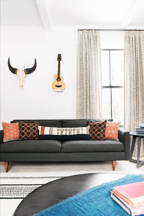 Boho chic living room matte black sofa with textural color throw pillows black white area rug small prints curtains decorative quitar decorative animal skull