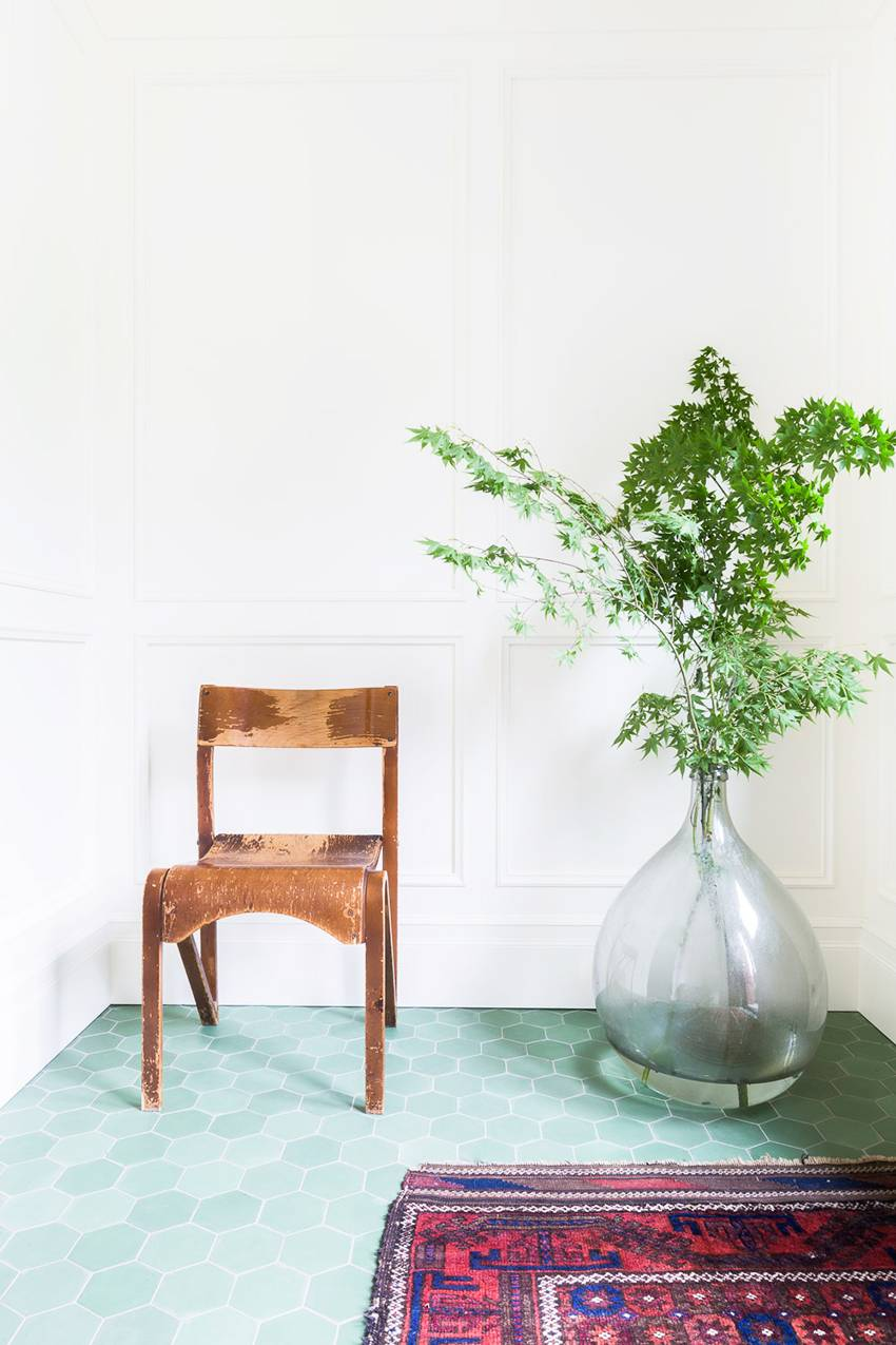 bigger houseplant with clear glass pot wooden chair multocolored runner hexagon tile floors in green