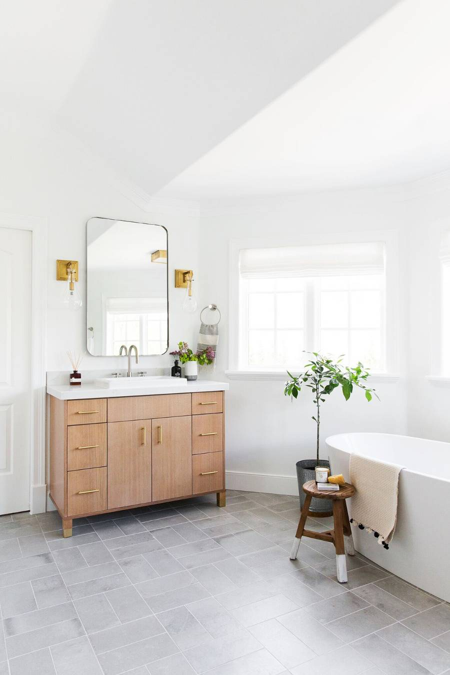 bright and cheery bathroom design freestanding tub in white wooden stool fresh potted greenery white top bathroom vanity with wood surface cabinets system frameless mirror concrete tiled floors