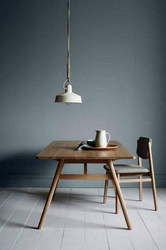 dark gray wall paint simple mid century modern dining table made of wood wood dining chair long hang pendant with white lampshade