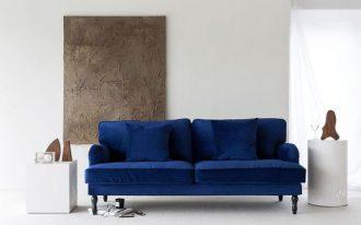 deep navy blue velvet sofa with wood legs deep navy blue velvet throw pillows abstract oil painting white minimalist side tables