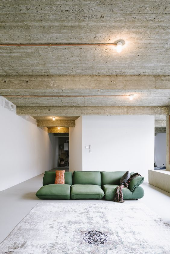 floor sofa in green throw blanket white washed floors wood ceilings white wall painting