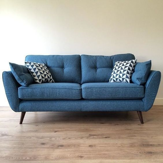 midcentury modern sofa in blue with angled wood legs blue throw pillows deep blue white throw pillows