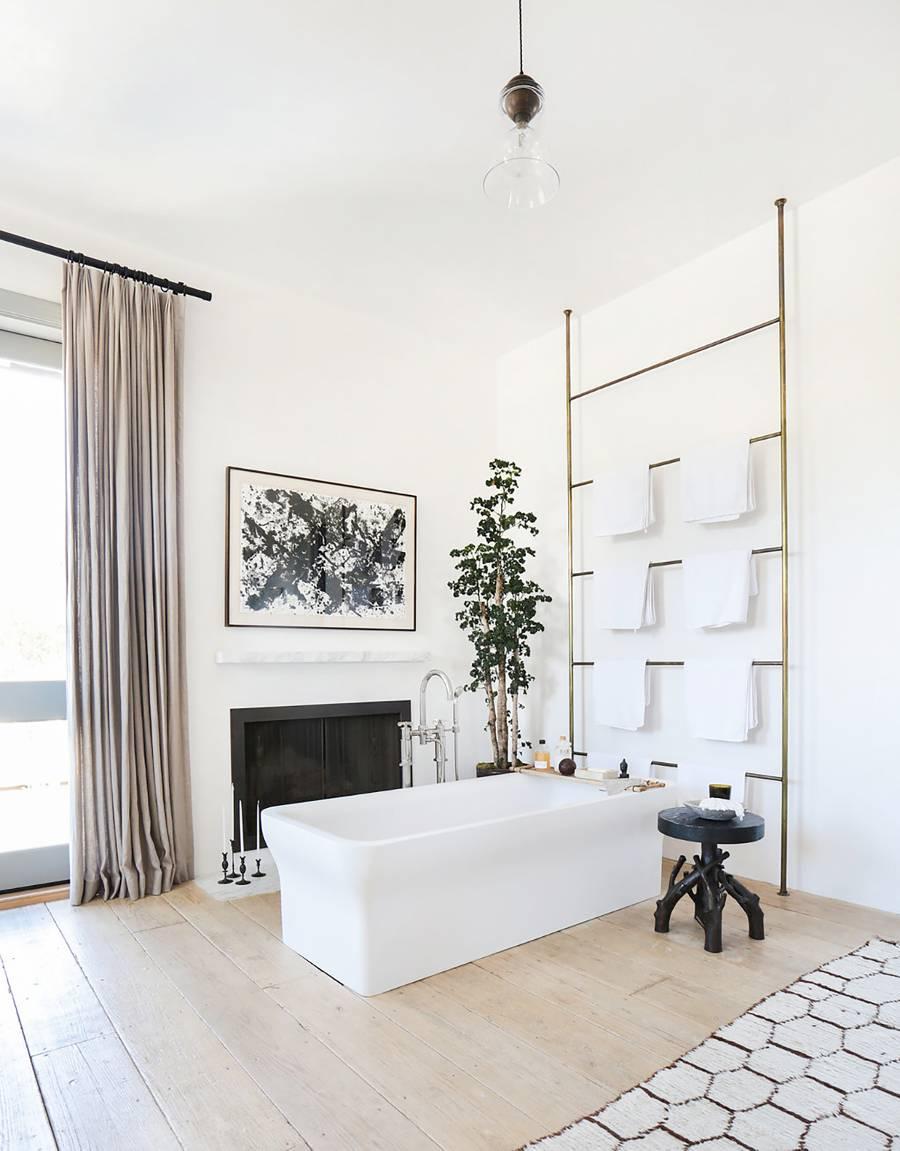 modern and glamorous bathroom gold toned towel rack black painted stool modern white bathtub recessed fireplace full length curtains light wood floors
