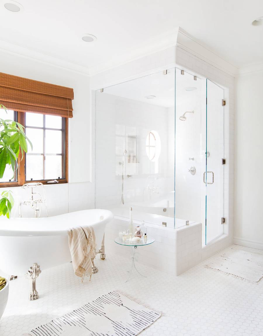 modern retro bathroom in dominant white classic flawfoot bathtub in white glass round top stool white bath mat walk in shower with clear glass door