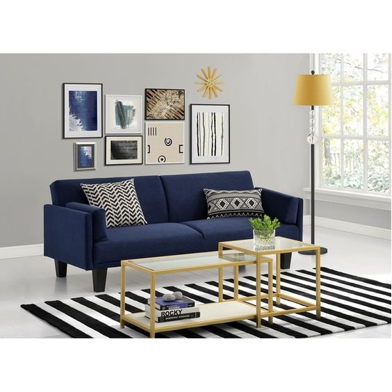modern sofa in navy blue throw pillows in monochrome modern white coffee tables with gold toned construction striped area rug in black white gray wall paint