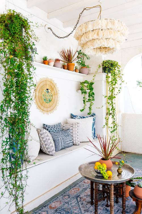 seating corner with white back walls green vines decoration Moroccan area rug Moroccan coffee table stunning chandelier