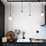 Series Of Bulb Light Fixtures With Differing Heights White Subway Tile Walls Black Washed Kitchen Cabinetry Undermount Sink In White Block Butcher Cutting Board