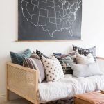 Simple Cozy Living Room Daybed Like Sofa With Lots Of Throw Pillows Fabric Covered Ottoman Black White Area Rug Chalkboard Wall Art With Map