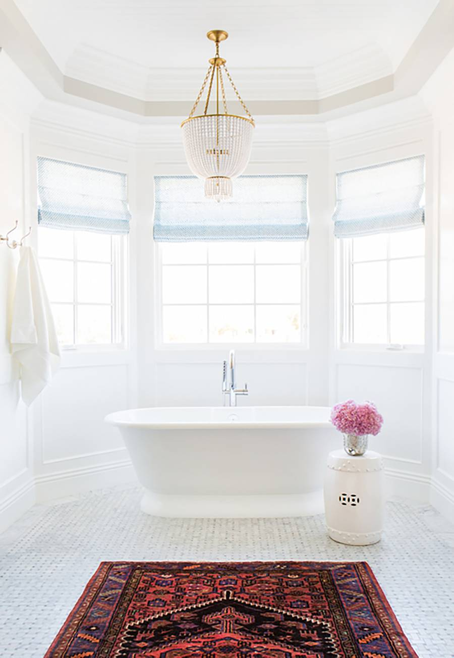 simple yet elegant master bathroom in all white purely white bathtub traditional area rug white stool pink flowers on glass pot crystal chandelier