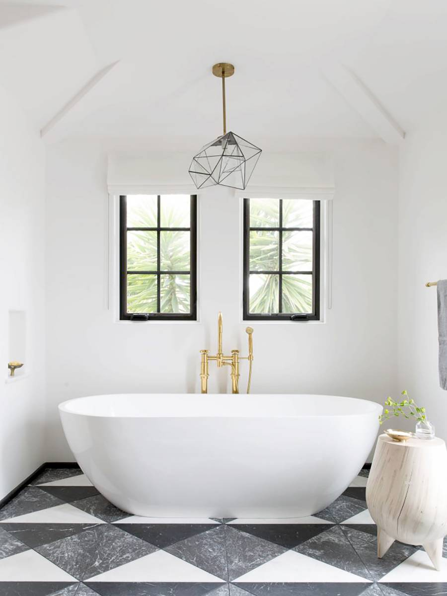 stylish and contemporary bathroom with a couple of windows white bathtub with gold toned faucets monochrome tile floors light wood stool trendy pendant