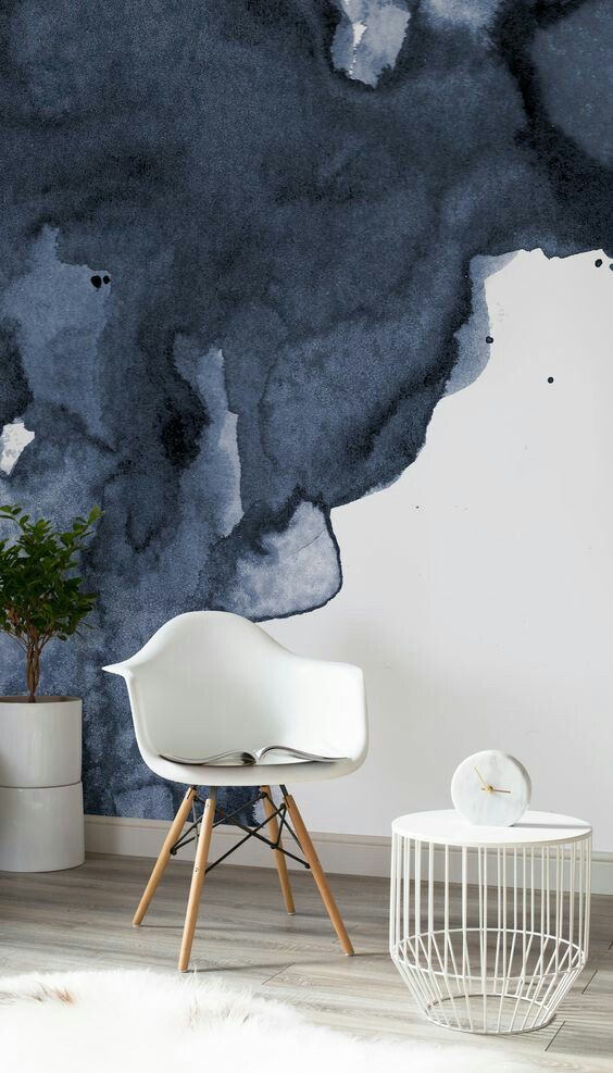 abstract watercolor mural in dark blue midcentury modern chair in white midcentury modern coffee table with cage like base in white