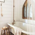 Bathroom With Victorian Charms Clawfoot Bathtub In White Hardwood Stool With Round Top Throw Blanket Semi Transparent Shower Curtains Brass Piping Wood Board Walls Herringbone Tile Floors