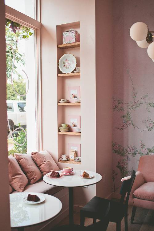 bay window idea built in window with pink throw pillows round marble top table black painted chair recessed display racks