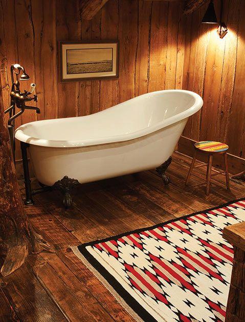 clawfoot bathtub in white multicolored area rug rainbow stool spotlight fixtures wood walls and floors