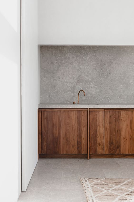 clean look kitchen design concrete backsplash minimalist wood kitchen cabinetry white walls light toned floors light toned area rug