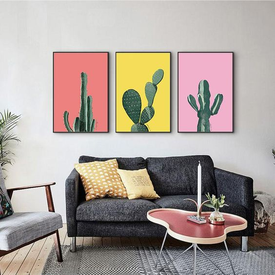 darker gray sofa with orange throw pillows assymmetrical coffee table with pink top bright and colorful cactus wall arts