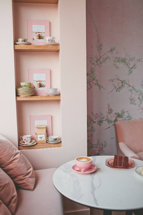 decorative vintage tea cups recessed racks marble top coffee table floral wallpaper in soft pink walls