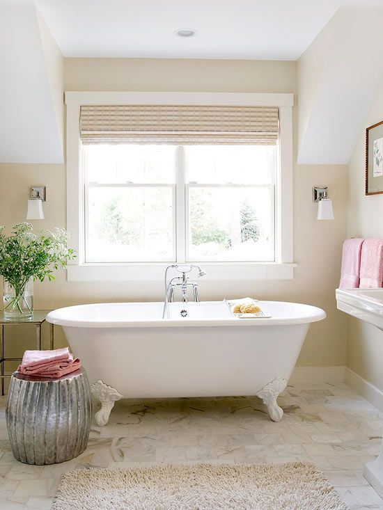 glass window with roll up shutter clawfoot bathtub in white silver toned pouf white tile floors broken white wool rug a couple of sconces