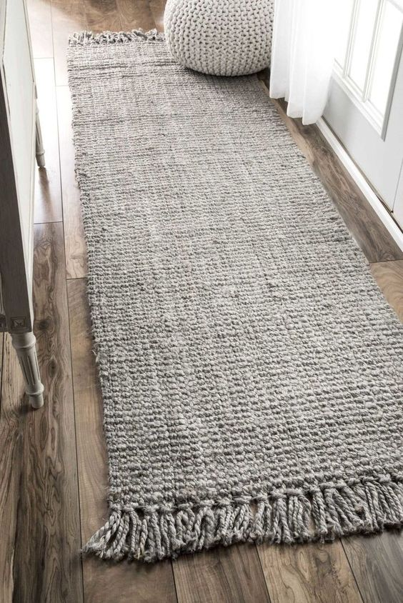 handmade knitted wool runner in pale gray woven pouf in light gray wood floors