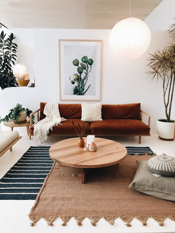 layered rugs brown sofa with white throw pillows and throw blanket round top wood coffee table gray floor pillow oversize orb pendants houseplants on pots
