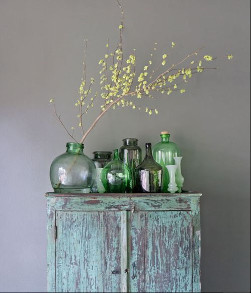light gray wall paint shabby bue storage solution in vintage style decorative glass vases in semi transparent green