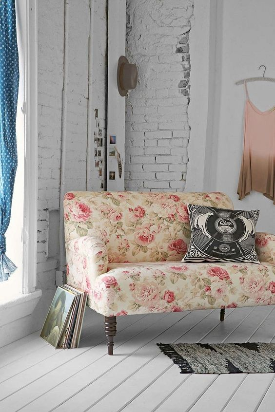 loveseat with romantic rose prints white wood board floors white painted brick walls