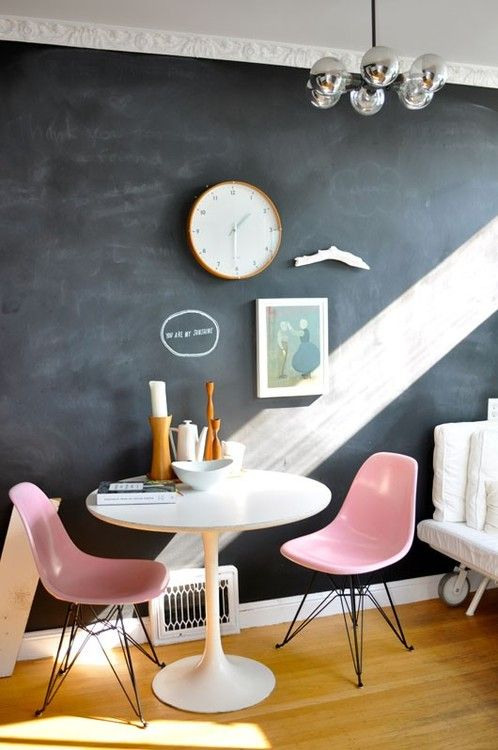 midcentury modern chairs in pink with angled hairpin legs round white top table chalkboard wall wood floors