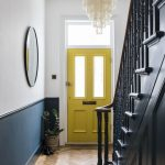 Modern Hallway With Victorian Touch Grand Crystal Chandelier Oversize Round Shape Wall Mirror With Brass Frame Herringbone Wood Floors Yellow Pop Front Door