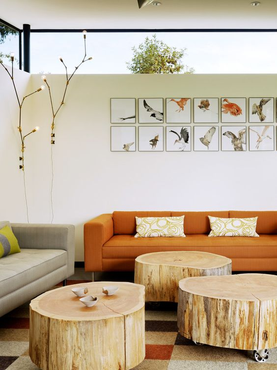 pale toned log coffee tables orange sofa in modern style well ordered wall arts in frames tree lighting fixtures
