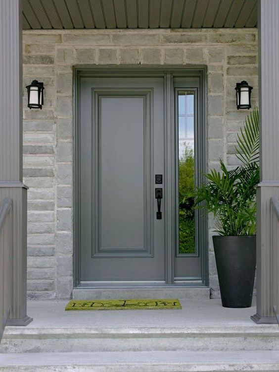 paneled front door in gray with glass side window square shaped stone exterior walls a couple of exterior wall sconces green door mat