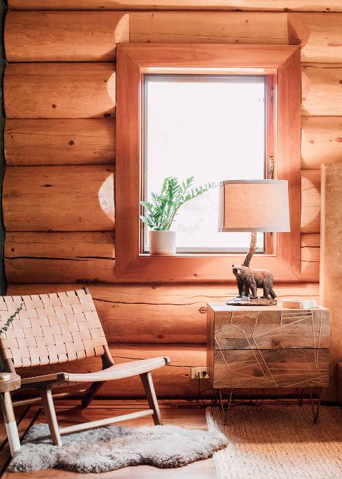 reading corner idea reading chair with leather woven detail warm fur mat square shaped log table bear table lamp glass window white potted greenery