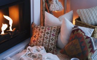 reading nook nearest fireplace layers of throw pillows with various colors and prints white throw blanket woven basket for storage