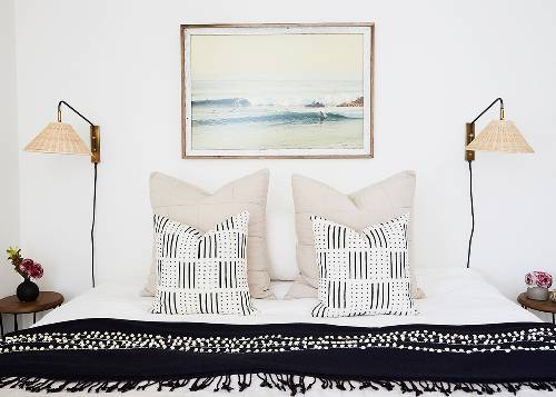 sea painting as the centerpiece of room a couple of wicker sconces black white pillowcases white taupe pillowcase dominant black comforter