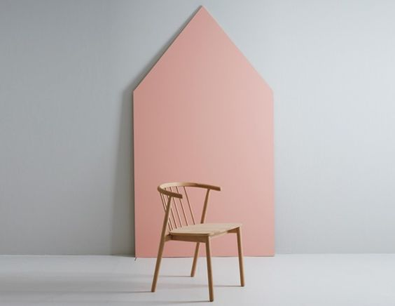 simple wood chair crisp white wall with pointeds shape accent color in pink