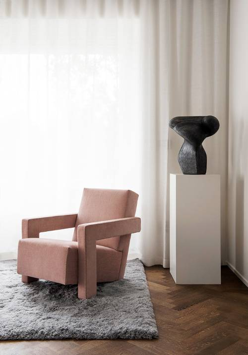 stylish chair in soft pink thick area rug in gray herringbone patterned wood floors white window curtains minimalist interior decoration in white black