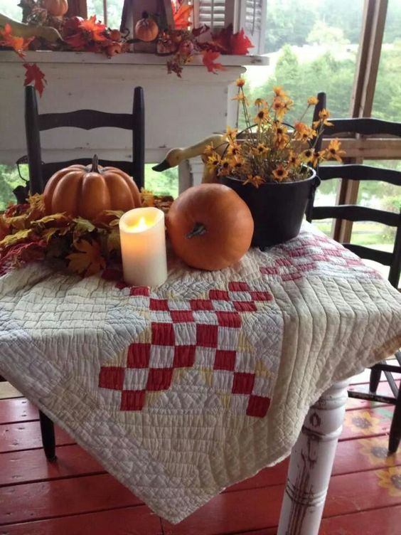 textural quilt like table cover with red square accents