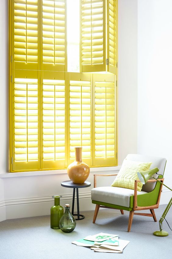 vividly yellow window shutter bright green chair with wood structure blue side table with round top