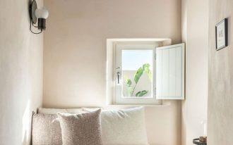 white interior bedroom smaller window smaller futon white pillows