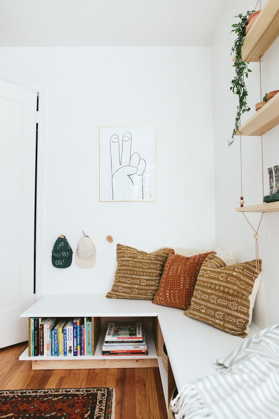 white interior reading nook L shaped  bench seat in white with under bookshelf