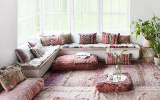 Leg less L shaped couch with Moroccan covered throw pillows floor seats with Moroccan motifs area rug with Moroccan motifs