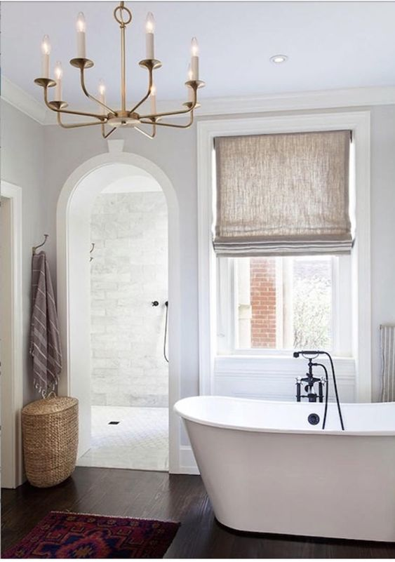 Roman shade in soft neutral tone white bathtub dark wood floors curved door without panel woven basket